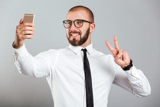Успешный зрелый человек в очках и галстуке, показывая знак мира, принимая селфи на смартфоне, изолированных на серую стену
