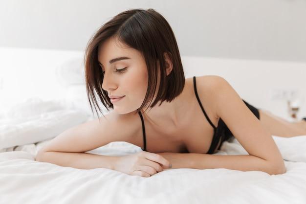 ベッドで横になっている魅力的な若い女性の肖像画