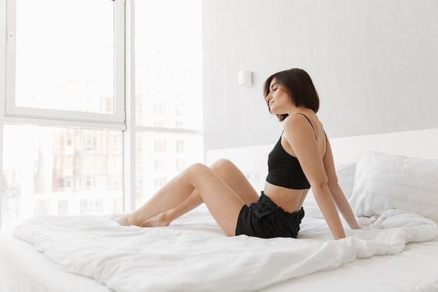 ベッドの上に座っている若い女性の肖像画