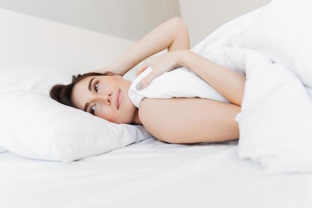 枕の上に横たわる幸せな若い女の肖像