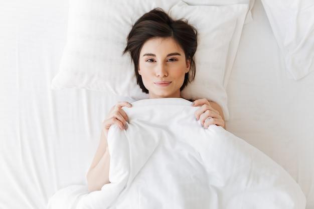 枕の上に横たわる素敵な若い女性の上面図の肖像画