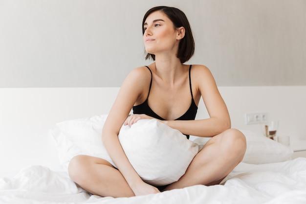 枕で座っている素敵な若い女性の肖像画