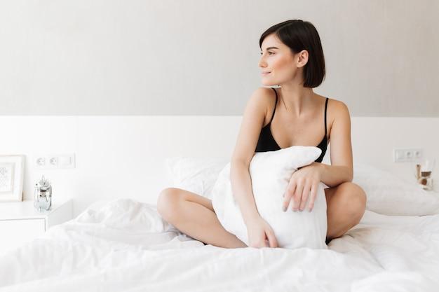 枕と座っている笑顔の若い女性の肖像画