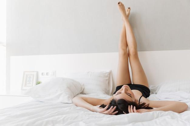 足でベッドに横たわっている美しい若い女性の肖像画