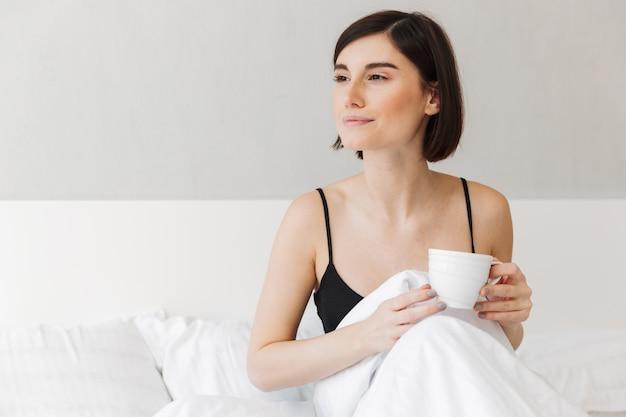 一杯のコーヒーを保持しているかなり若い女性の肖像画