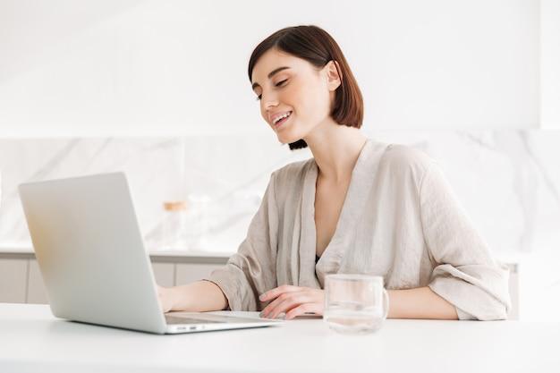 Портрет кавказской взрослой женщины носить халат, улыбаясь и работает, или в чате на белом ноутбуке в квартире