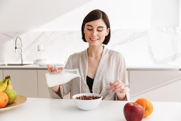 ホテルの部屋のキッチンで朝食をとり、ミルクでココアボールを食べるブルネットの若い女性の画像