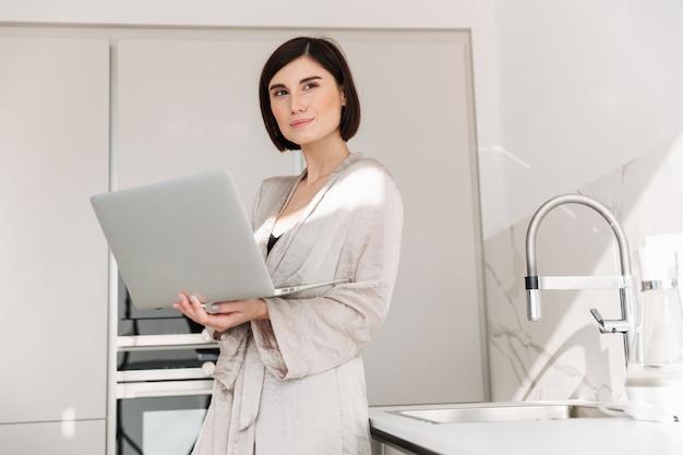 Портрет кавказской взрослой женщины носить халат, улыбаясь и работает, или общение онлайн на белом ноутбуке в квартире