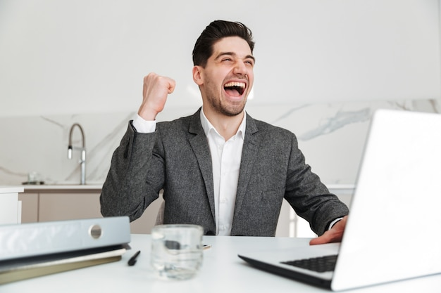 Портрет веселого делового человека, радуясь и сжимая кулак, сидя в офисе и работая на ноутбуке