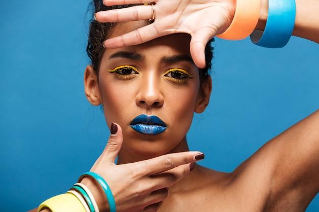 カラフルな化粧と青い壁の上の分離されたファッションの外観とカメラでジェスチャーのパンで巻き毛の横の派手なムラートの女性
