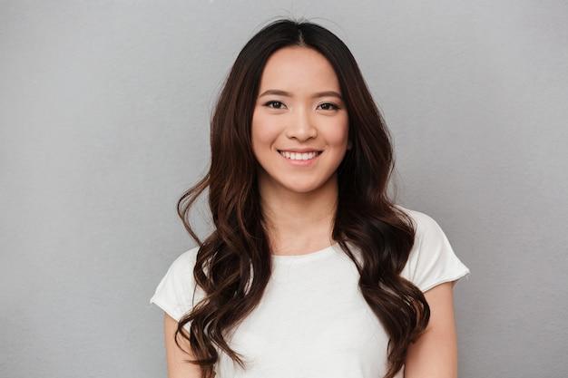 Портрет азиатской прекрасной женщины с темными вьющимися волосами позирует с доброй улыбкой, изолированных на серую стену