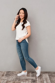Положительная азиатская женщина в вскользь футболке и джинсах имея говорить на мобильном телефоне, изолированном над серой стеной