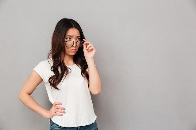Удивленная женщина в футболке и очках держит руку на бедре