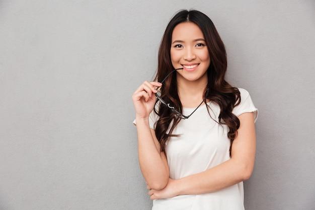 Счастливая азиатская женщина в тенниске укусов футболки