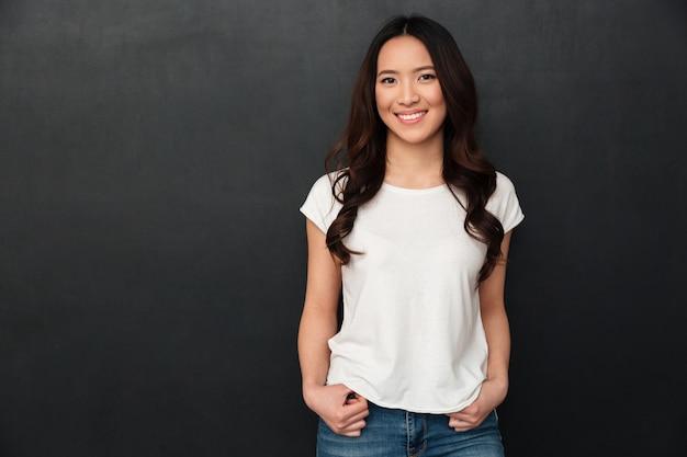 Счастливая азиатская женщина в представлять футболки и