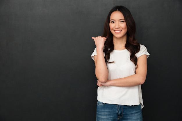 Улыбаясь азиатские женщины в футболке, указывая прочь