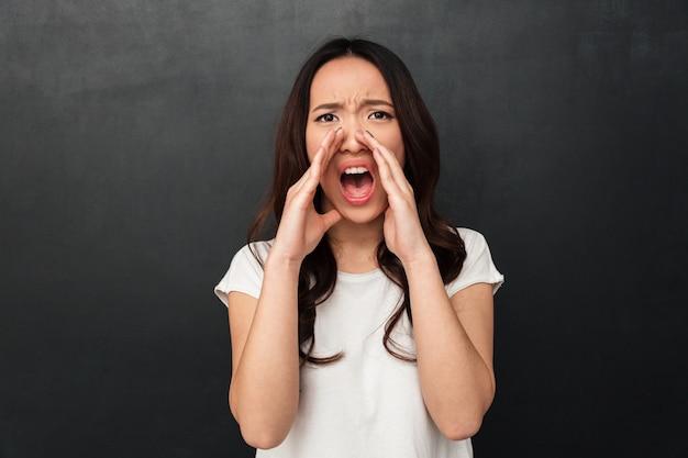 Эмоциональная азиатская женщина в повседневной футболке кричать или звонить с тревогой, положив руки в рот, изолированные над темно-серой стеной