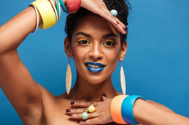 カラフルなメイクと分離された青い壁の上の彼女の腕にアクセサリーを示すパンの巻き毛を持つ水平素敵なムラートの女性