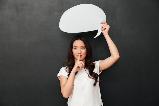 Тайна азиатская женщина в футболке, холдинг пустой речи пузырь