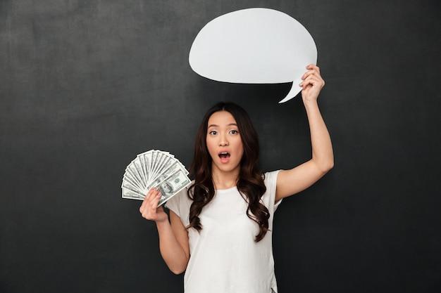 Шокирован женщина в футболке, держа деньги и пустой речи пузырь