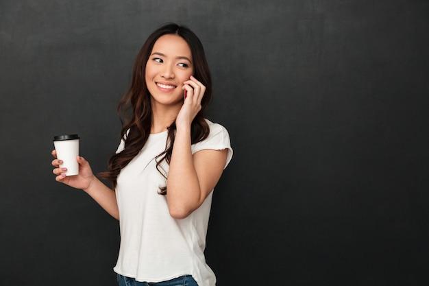 Улыбаясь азиатские женщины в футболке, держа чашку кофе