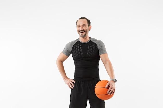 バスケットボールを保持している幸せな成熟したスポーツマンの肖像画