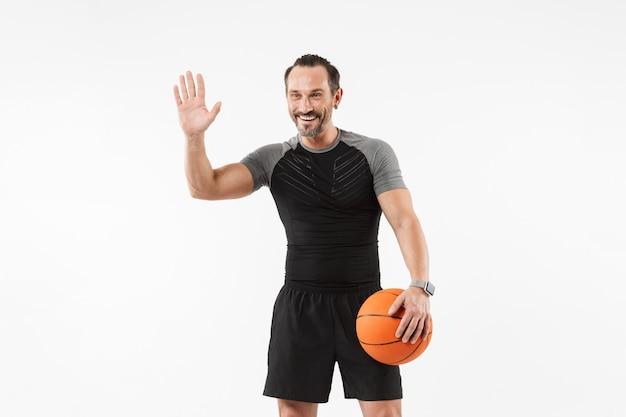 バスケットボールを保持している笑顔の成熟したスポーツマンの肖像画