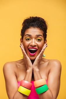 明るい化粧とアクセサリーの黄色の壁の上の顔に手のひらを置く垂直うれしそうな半分裸ムラート女性