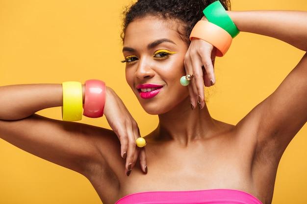 黄色の壁を越えて分離された彼女の手に宝石を示す明るいメイクと魅力的なアフリカ系アメリカ人女性のファッションの肖像画