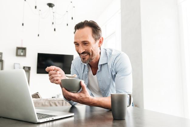 健康的な朝食を持つ笑顔の成熟した男