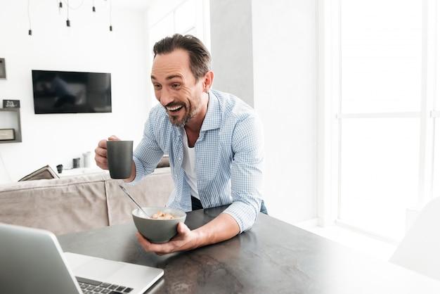 健康的な朝食を持つ興奮した中年の男性