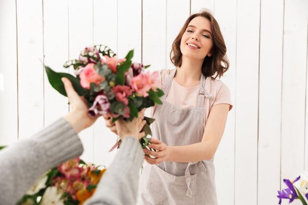 バイヤーとのワークショップで花と立っている花屋の女性。