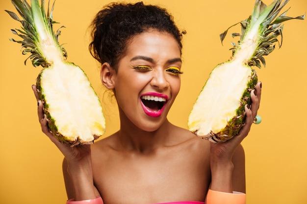 黄色の壁の上の半分に分離された新鮮なパイナップルを保持しているファッションの外観を持つ幸せな混血の女性の肖像画