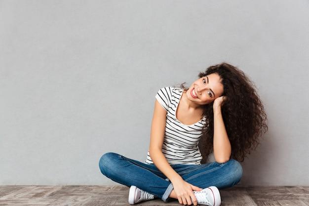灰色の壁を越えて幸せと率直な手で彼女の頭を支える床にロータスポーズで座っているカジュアルな服装で巻き毛の女性の肖像画間近します。