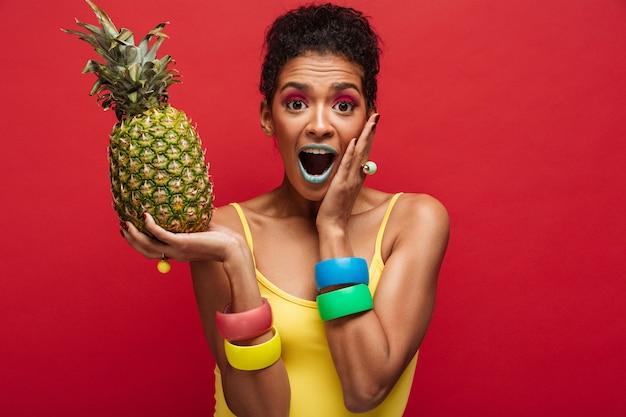 赤い壁の上の果物を楽しんで新鮮なジューシーなパイナップルを手で押しながら興奮しているカラフルな衣装でムラートの女性