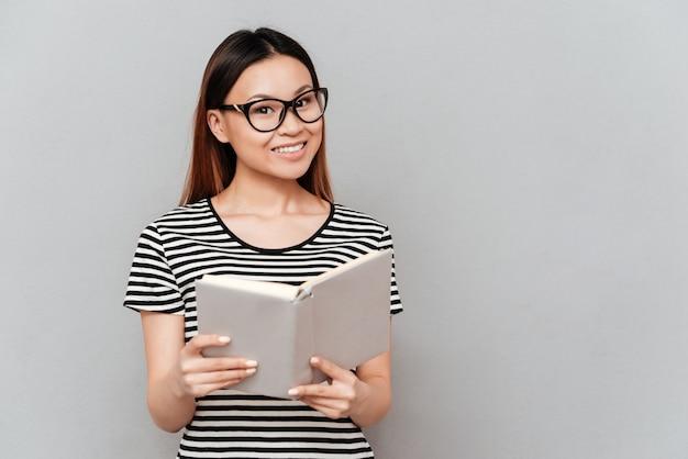 本を読んでメガネの若いアジア女性