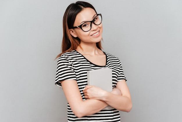 ノートパソコンを探しているカメラで眼鏡をかけている若い学生女性