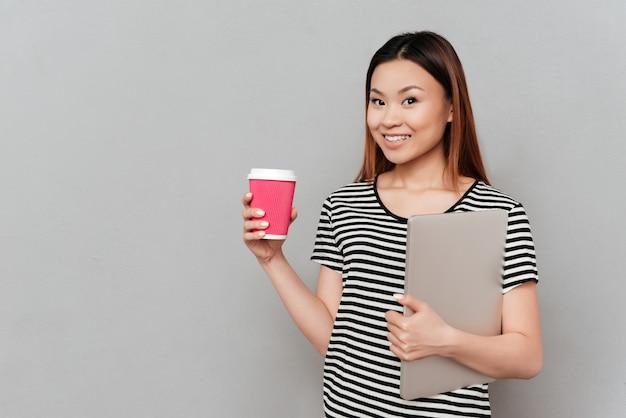 一杯のコーヒーとラップトップを保持している若い女性