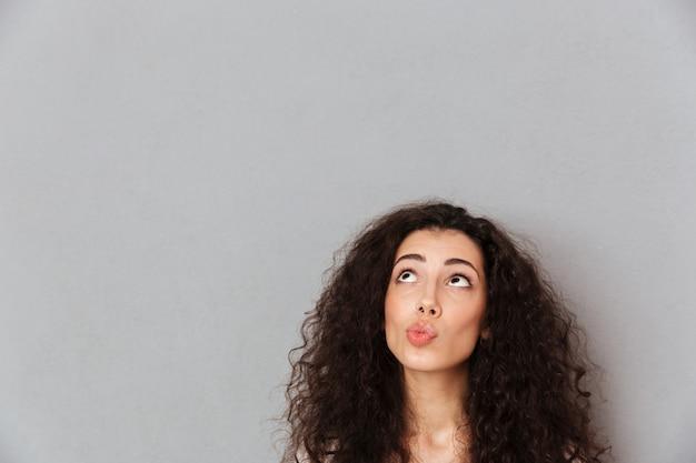 灰色の壁の上のねじれた唇で見上げるクールな巻き毛のヘアスタイルを持つきれいな女性の肖像画間近します。
