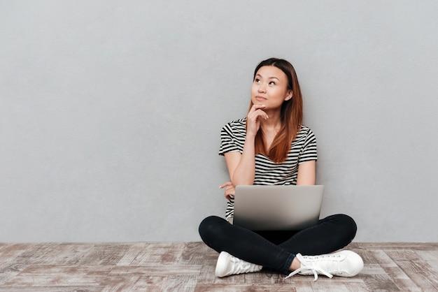 ノートパソコンで床に座って夢を見ている若い女性