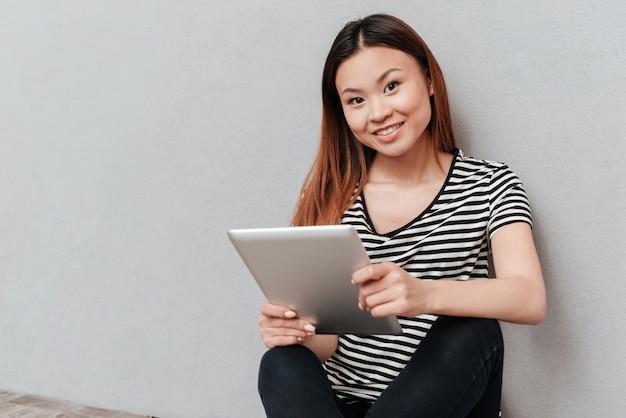若いアジア探しているカメラとラップトップを使用しながら笑顔