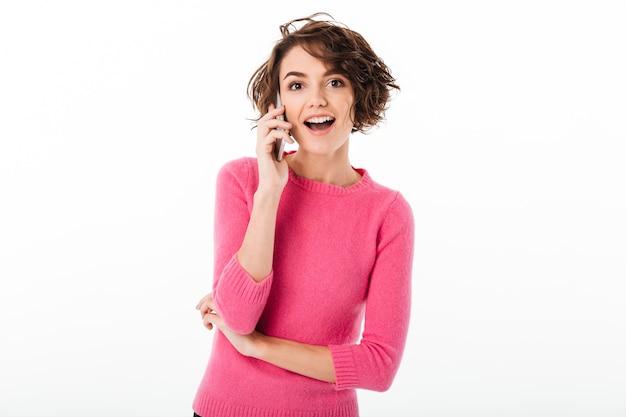Портрет жизнерадостной привлекательной девушки держа мобильный телефон