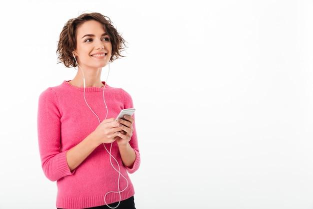 Портрет улыбающейся молодой девушки, слушающей музыку