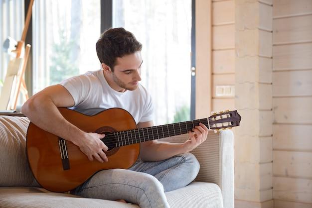 ソファに座ってギターを持つ男