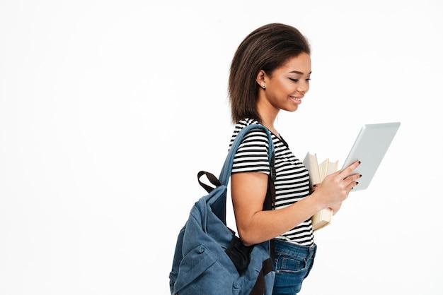 Усмехаясь милая африканская женщина студента с рюкзаком используя таблетку пк