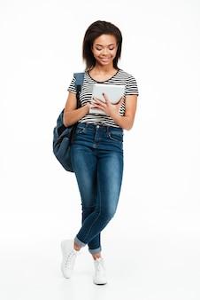 Рюкзак счастливой милой подростковой женщины нося и таблетка пк использования