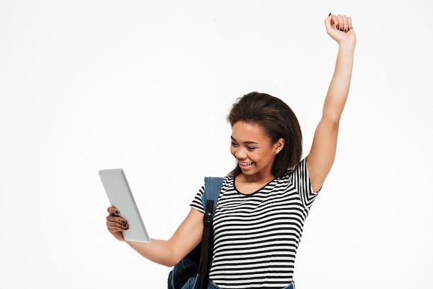 Счастливая афро американская подростковая женщина с рюкзаком держа пк