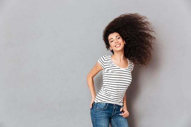Великолепная женщина в полосатой футболке развлекается, махая своими красивыми волосами, радуясь и радуясь серой стене