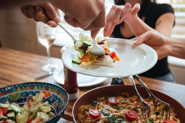 Люди кладут еду на тарелку и обедают вместе