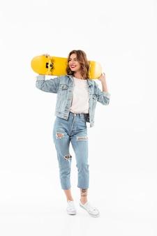 スケートボードを押しながら白い壁に目をそむけるデニムの服で完全な長さの笑顔の女性